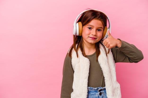 Mała kaukaska dziewczynka słucha muzyki na różowym tle, uśmiechając się i podnosząc kciuk do góry