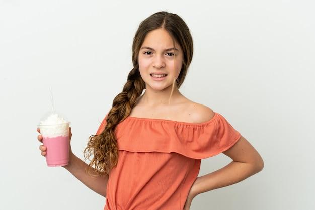 Mała kaukaska dziewczynka z truskawkowym koktajlem mlecznym na białym tle cierpiąca na ból pleców za wysiłek