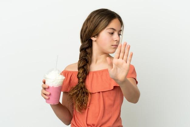 Mała kaukaska dziewczynka z truskawkowym koktajlem mlecznym na białym tle robiąca gest zatrzymania i rozczarowana