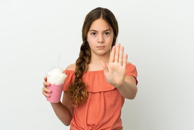 Mała kaukaska dziewczynka z truskawkowym koktajlem mlecznym na białym tle robiąca gest zatrzymania