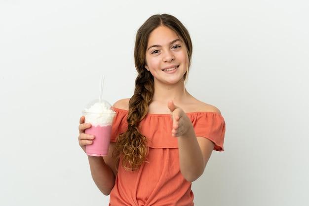 Mała kaukaska dziewczynka z truskawkowym koktajlem mlecznym na białym tle, ściskając ręce, aby zamknąć dobrą ofertę
