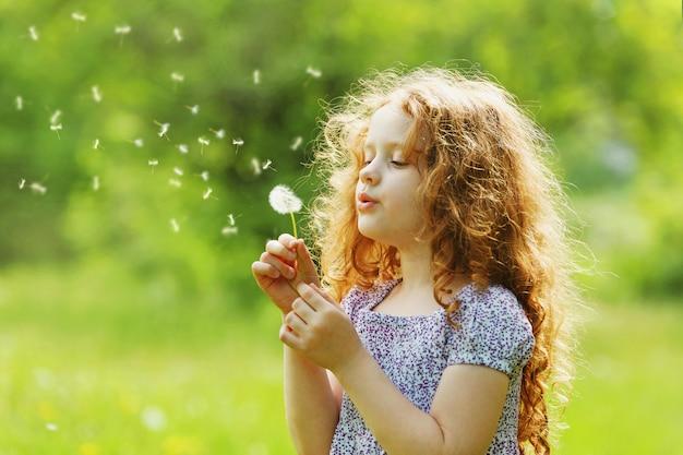 Mała kędzierzawa dziewczyna podmuchowy dandelion.
