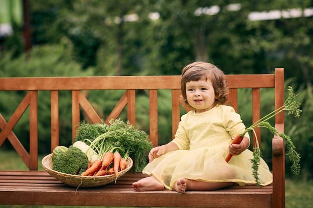 Mała kędzierzawa dziewczyna w żółtej sukience, boso, trzyma w dłoni marchewkę, siedzi na ławce obok dużego kosza warzyw z cukinią, marchewką i brokułami. zdrowe jedzenie, zielone wegetariańskie jedzenie.