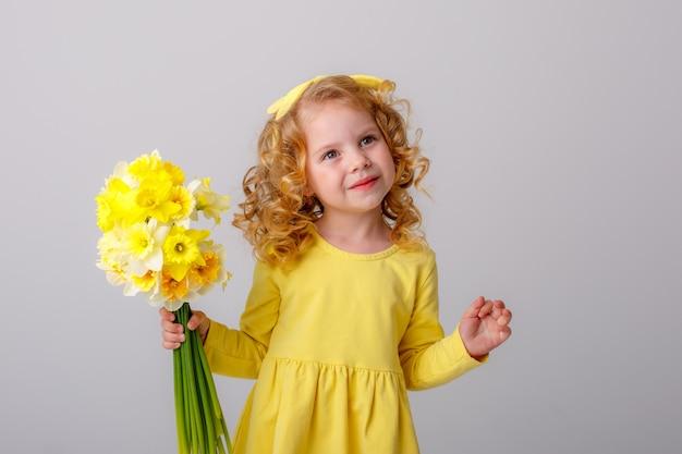 Mała kędzierzawa dziewczyna w żółtej sukience z bukietem wiosennych kwiatów na białej przestrzeni uśmiecha się