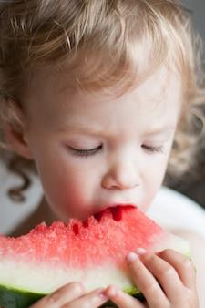 Mała kędzierzawa dziewczyna z przyjemnością je plasterek arbuza w lecie