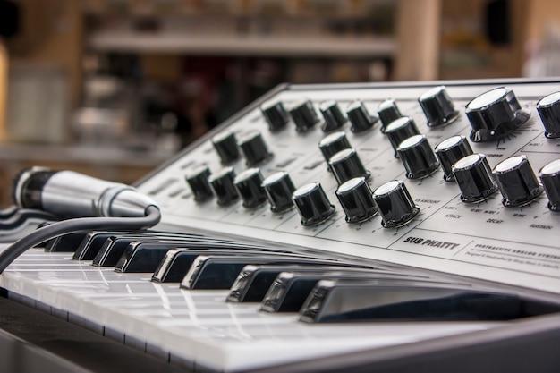 Mała klawiatura muzyczna w stylu vintage z potencjometrami do regulacji dźwięku i mikrofonem do śpiewania.