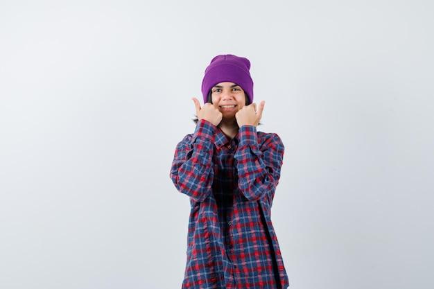 Mała kobieca czapka pokazująca kciuki w górę, wyglądająca na radosną