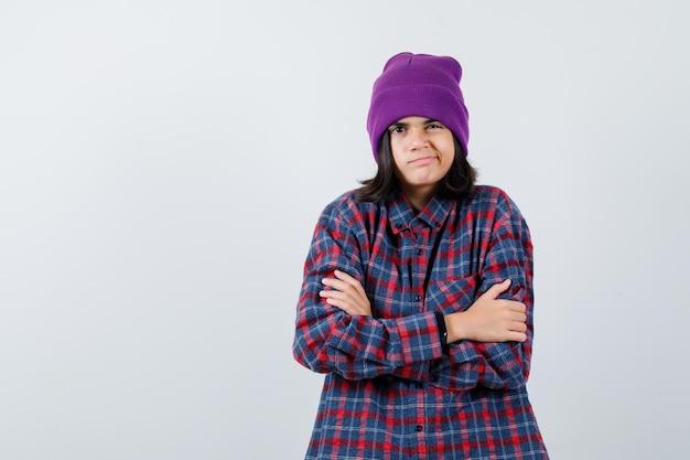 Mała kobieca czapka przytulająca się, wyglądająca na schłodzoną