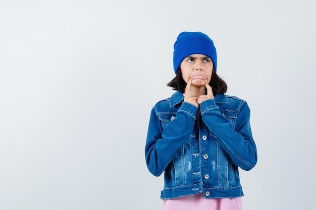 Mała kobieta ciągnie policzki palcami w koszulce, dżinsowej kurtce i czapce
