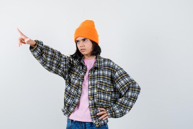 Mała kobieta odwracająca wzrok, trzymająca rękę na biodrze w t-shircie, wyglądająca pewnie