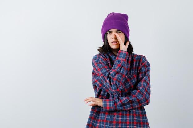 Mała kobieta opowiadająca sekret za czapką wygląda poważnie