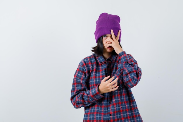 Mała kobieta patrząca przez palce czapka wygląda poważnie