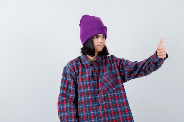 Mała kobieta pokazując kciuk w górę czapka wygląda pewnie