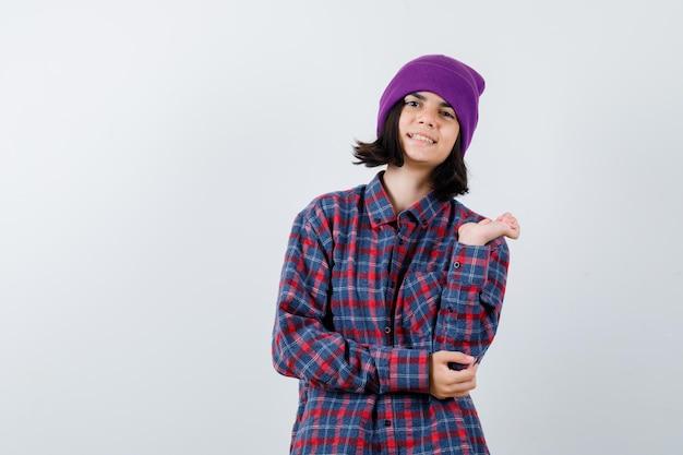 Mała kobieta pokazująca coś w czapce wygląda na szczęśliwą