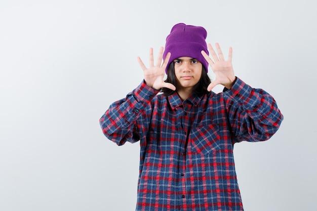Mała kobieta pokazująca dłonie w kraciastej koszuli i czapce wygląda poważnie