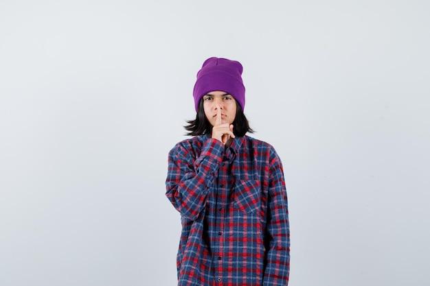 Mała kobieta pokazująca gest ciszy czapka wyglądająca pewnie