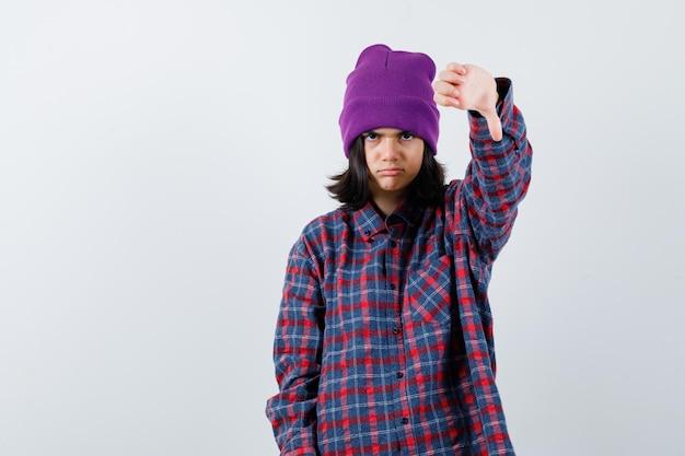 Mała kobieta pokazująca kciuk w dół czapka wygląda na niezadowoloną