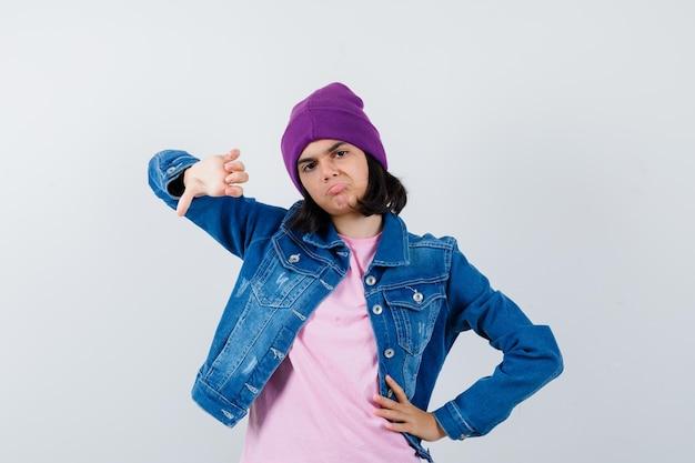 Mała kobieta pokazująca kciuk w dół, trzymająca rękę na biodrze w koszulce, wyglądająca na niezadowoloną