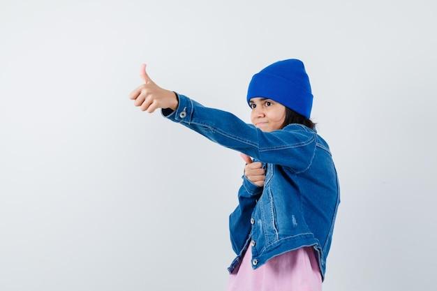 Mała kobieta pokazująca kciuki w górę w dżinsowej kurtce t-shirt, wyglądająca wesoło