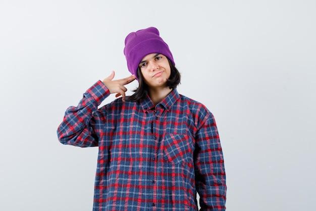 Mała kobieta robi gest samobójczy w kraciastej koszuli i czapce wyglądającej beznadziejnie