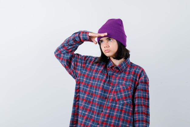 Mała kobieta trzymająca rękę, aby wyraźnie widzieć w kraciastej koszuli i czapce, wyglądająca na pewną siebie