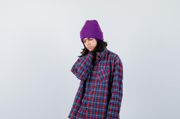 Mała kobieta trzymająca rękę na czapce pod szyją wygląda na wyczerpaną