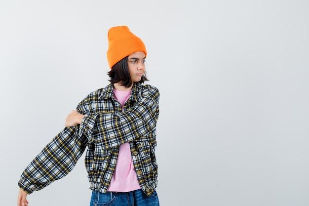 Mała kobieta trzymająca rękę na ramieniu w czapce z t-shirtem, wyglądająca pewnie