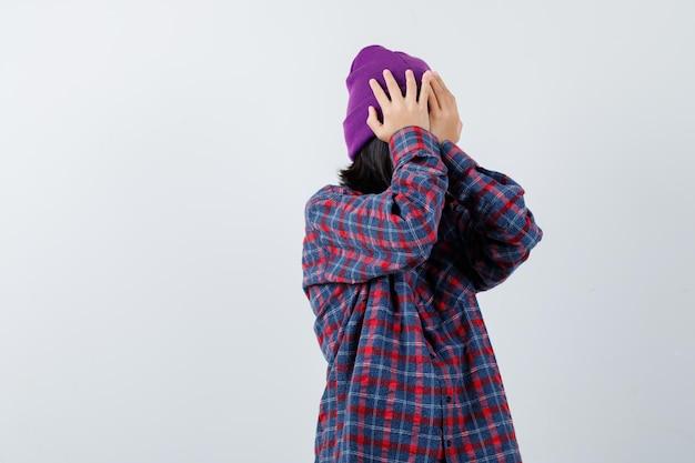Mała kobieta trzymająca się za ręce na głowie w kraciastej koszuli i czapce wyglądająca na zapominalską