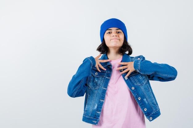 Mała kobieta trzymająca się za ręce na klatce piersiowej w koszulce i dżinsowej kurtce, wyglądająca na dumną