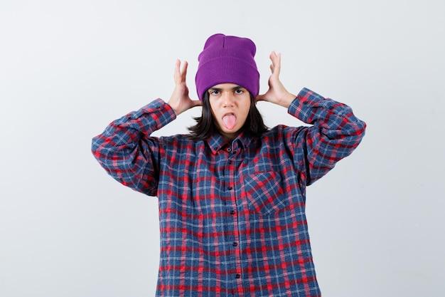 Mała kobieta trzymająca się za ręce nad głową w kraciastej koszuli i czapce wyglądającej śmiesznie