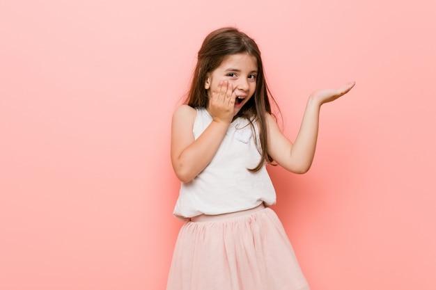 Mała kobieta ubrana w wygląd księżniczki posiada kopię miejsca na dłoni, trzymając rękę na policzku. zaskoczony i zachwycony.