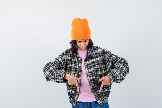 Mała kobieta w beanie t-shirt kurtka skierowana w dół, wyglądająca pewnie