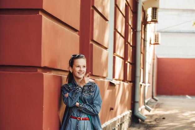 Mała kobieta w dżinsach ubrania stoi w pobliżu starego czerwonego budynku