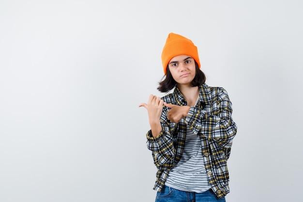 Mała kobieta w koszulce i kurtce, wskazując kciukiem na prawą stronę
