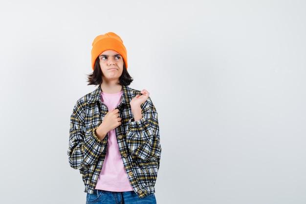 Mała kobieta w koszulce odwracająca wzrok, trzymająca przed sobą ręce