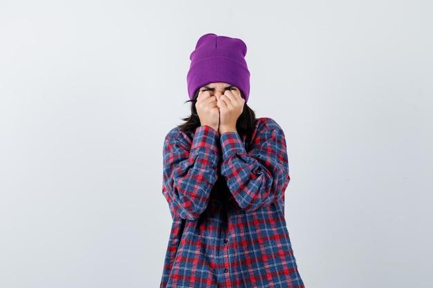 Mała kobieta w kraciastej koszuli i czapce stoi w przerażonej pozie i wygląda na przestraszoną