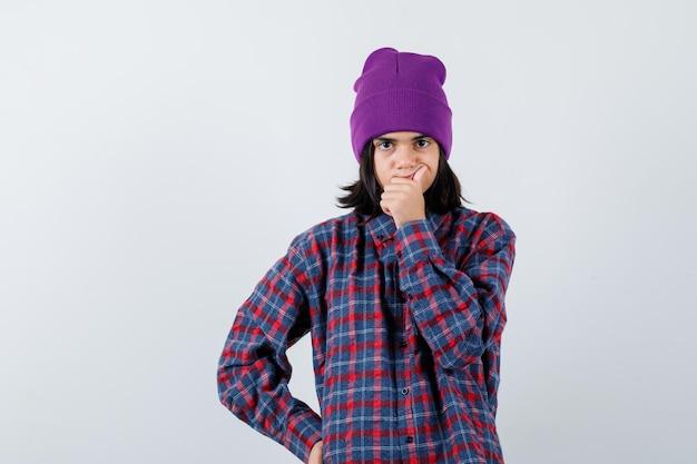 Mała kobieta w kraciastej koszuli i czapce, trzymająca dłoń na ustach, wyglądająca na zamyśloną