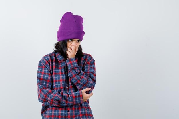 Mała kobieta w kraciastej koszuli i czapce, trzymająca rękę na ustach, wyglądająca na zdziwioną