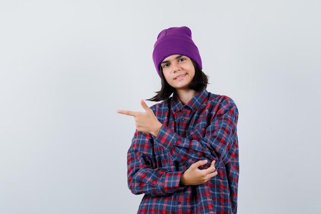 Mała kobieta wskazująca na lewą stronę w kraciastej koszuli i czapce wygląda na szczęśliwą