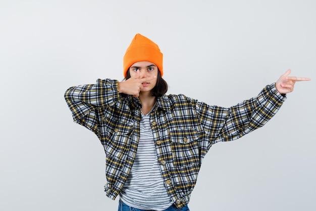 Mała kobieta wskazująca na prawą stronę w koszulce i kurtce, która wygląda pewnie
