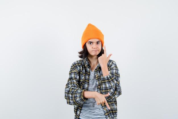 Mała kobieta wskazująca w górę iw dół w czapce z t-shirtem, wyglądająca pewnie