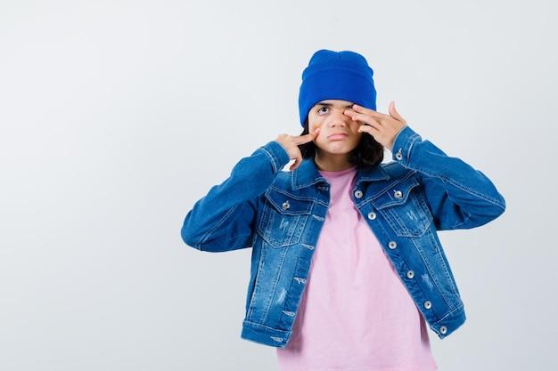 Mała kobieta zakrywająca oko ręką, naciskając policzek palcem
