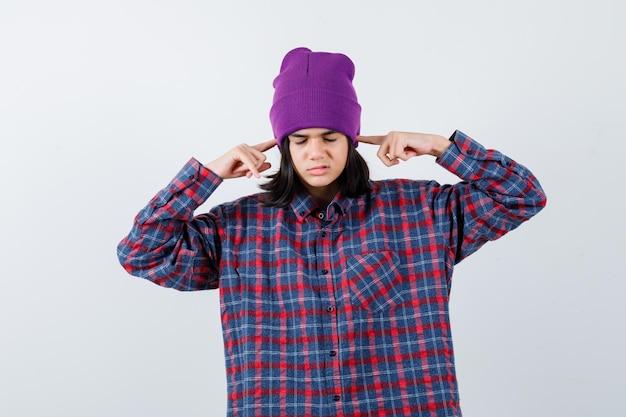 Mała kobieta zatykająca uszy palcami w kraciastej koszuli i czapce wyglądająca na zirytowaną