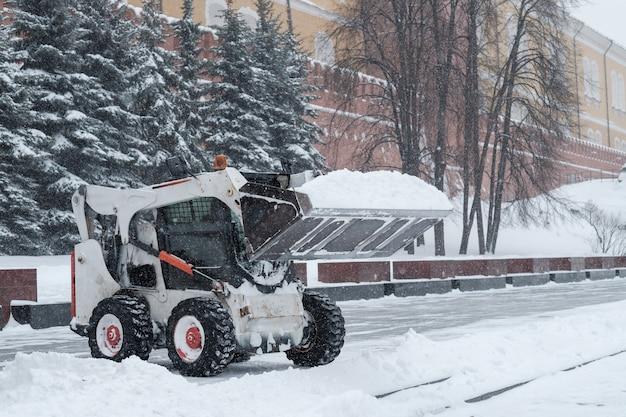 Mała koparka ładowarkowa usuwa śnieg z chodnika w pobliżu murów kremla podczas obfitych opadów śniegu