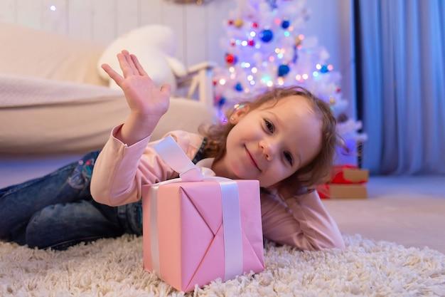 Mała kręcona dziewczyna z prezentem, boże narodzenie