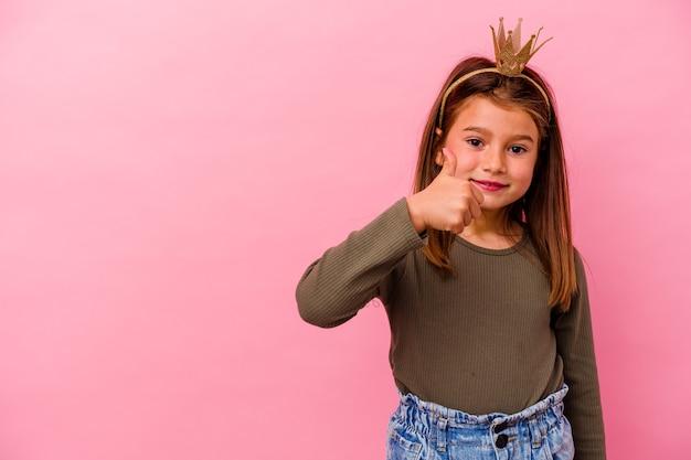 Mała księżniczka dziewczyna z koroną na białym tle na różowej ścianie, uśmiechając się i podnosząc kciuk do góry