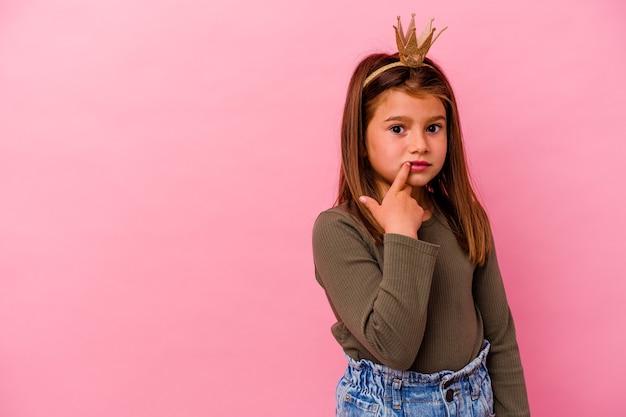 Mała księżniczka dziewczyna z koroną na białym tle na różowo zrelaksowany myślenie o czymś, patrząc na przestrzeń kopii.
