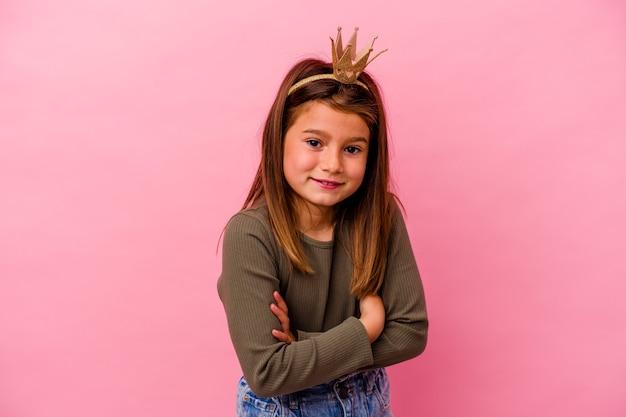 Mała księżniczka dziewczyna z koroną na białym tle na różowy śmiech i zabawę.