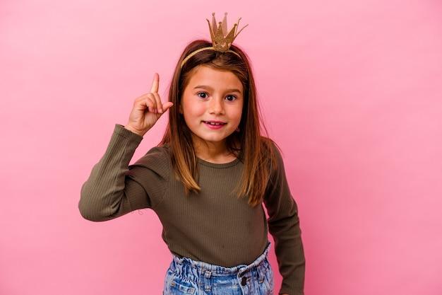 Mała księżniczka dziewczyna z koroną na różowym tle, mając pomysł