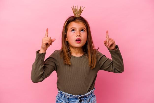 Mała księżniczka dziewczyna z koroną na różowym tle, wskazując do góry z otwartymi ustami.
